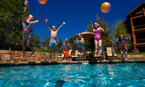 Kids jumping into swimming pool at Snowmass Club